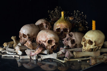 Pile of skulls with bone and pile of dry flowers and candle