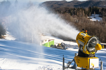 Snow cannon produces artificial snow on the ski slopes with a snow cat on background