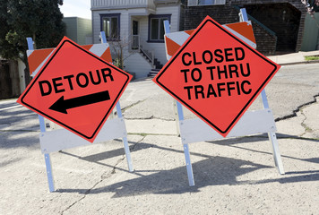 DETOUR AND CLOSED TO THRU TRAFFIC signs on steep hill.