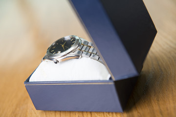 Great logging stainless steel watch in a blue box placed on the wooden table.