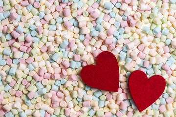 Two red hearts on colorful mini marshmallows background