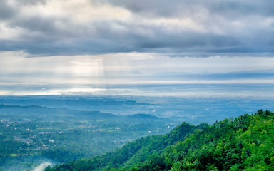 Majestic sun beam or god rays hitting the ground and forest, captured from the top. Captured from  Tranggulasih hill, Banyumas, Indonesia