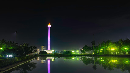 National Monument (Monas) at night, in front of big pool, create beautiful reflection of this monument., this is one of iconic monument in Jakarta, Indonesia