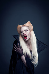 Beautiful blonde girl vampire with  blood is on the mouth and eyes wearing black clothes. Amazing hairstyle