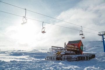 Snowcat, chairlift lift in sunny cold winter day
