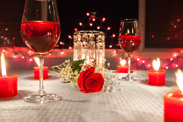Romantic dinner with wine, candles and a red rose on a table