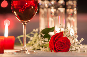 Romantic dinner with wine, candles and a red rose on a table.