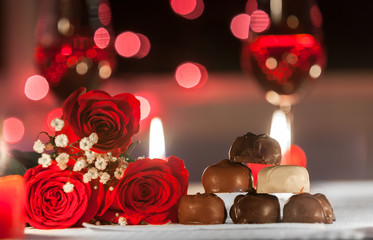 Red roses and chocolates in a romantic date night setting.