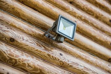 LED flashlight on a wooden log wall