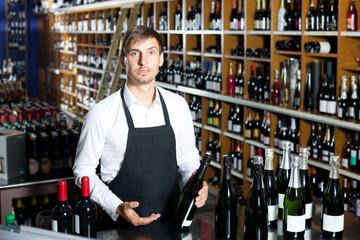 Man seller wearing uniform having bottle of wine