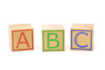 ABC letters on three brown wooden cubes lined up