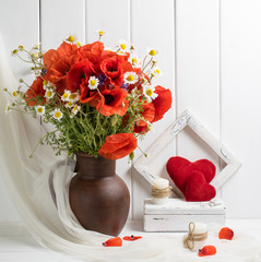 Red poppies in clay jug and hearts on wooden planks background