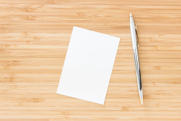 Notepaper with pen put on wooden desk