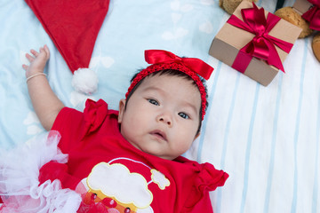 Cute little girl newborn with decorating Christmas tree