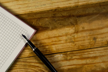 Notebook with fountain pen on a wooden table