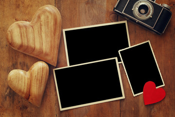 empty photo frames next to old camera and hearts