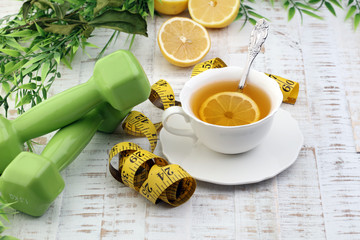 ginger tea - fitness liefestyle concept with tea, dumbells and measure tape