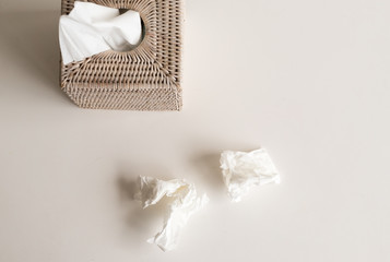 High angle view of white rattan tissue box and crumpled tissues on table - cold and flu season concept, grief concept