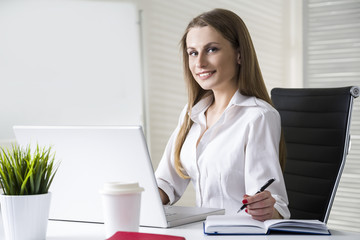 Close up of a smiling and beautiful businesswoman wearing a white blouse and sitting at her desk with a laptop. Mock up