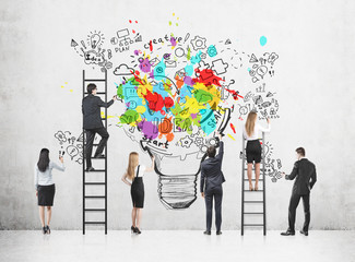 Rear view of a business people standing on ladders and floor near a concrete wall and drawing a colorful creative business idea sketch and a light bulb