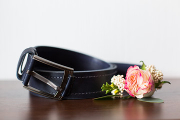 Groom's morning. Wedding accessories on wooden background. A belt, rings, watch, boutonniere. Preparing to wedding day