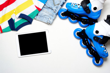 Sport, healthy lifestyle, roller skates and boy's clothing set, cell phone on white background