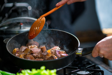 Man mixing the meat in a frying pan shovel