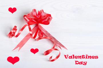 День Святого Валентина,красный бант,лента,надпись и сердечки на фоне светлого дерева.