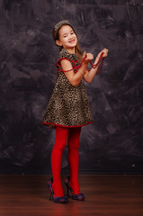 Pretty smiling little girl wearing beautiful dress. She is wearing red beads and holding them in hands. Studio shot.