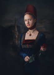 Portrait of a gorgeous girl in medieval era dress and headdress. Medallion in a shape of heart. Holding red rose in hands.