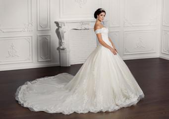 Fashion bride in luxury wedding dress amd diamond jewelry at studio
