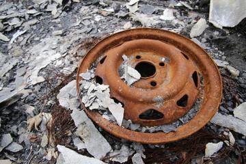 Car rim on a heap of debris