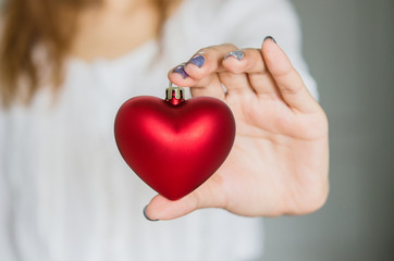 Young woman holding red heart decoration. Love concept.
