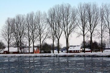 Houses on the Eenmskanaal with ice floes in Woltersum. The Netherlands