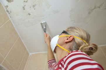 Blonde woman holding a plaster spatula, peeling a ceiling, preparing it for smoothing