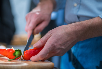 Man cutting red pepper