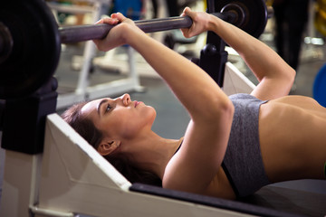 Sporty woman exercising with barbell in gym.