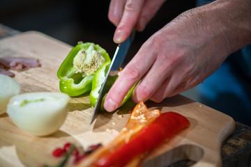 Man cuts pepper
