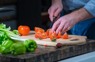 Man cuts a tomato