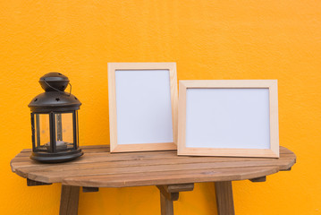 Two photo Frame and lamp on a wooden on Yellow background .
