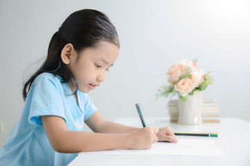 Portrait of Asian little girl drawing with pencil