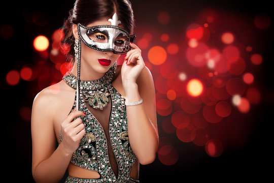 Beauty model woman wearing venetian masquerade carnival mask at party over holiday dark background. St valentine's day celebration. Glamour lady with perfect make up .