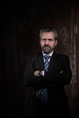 Portrait of a mature businessman on black background