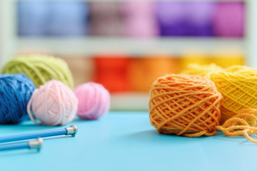 Knitting yarn and needles on blue table against blurred background.