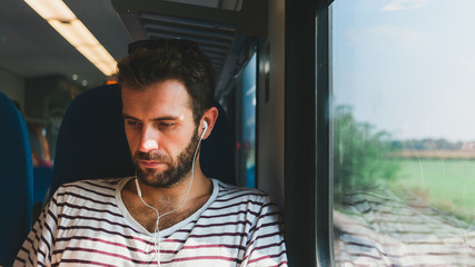 Young man traveling on a train sitting by the window listening to the music