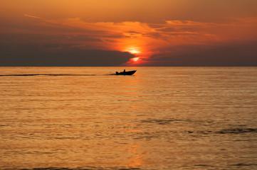 Boot am Horizont vor untergehender Sonne