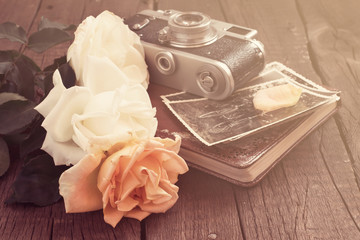 Bouquet of roses and old photo, retro camera  album.  Tinted,
