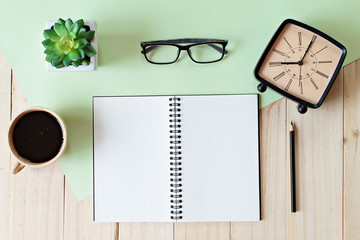 Still life, business, office supplies, education or vintage concept : Top view of working desk with blank notebook with pencil, coffee cup, eyeglasses, retro alarm clock and plant on wooden background