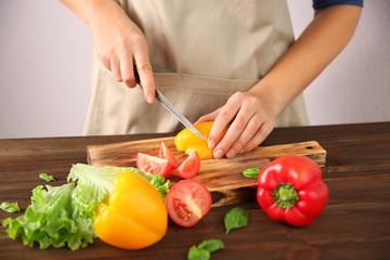 Woman chopping fresh vegetables on cutting board