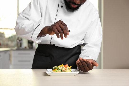 African American chef salting tasty salad in kitchen